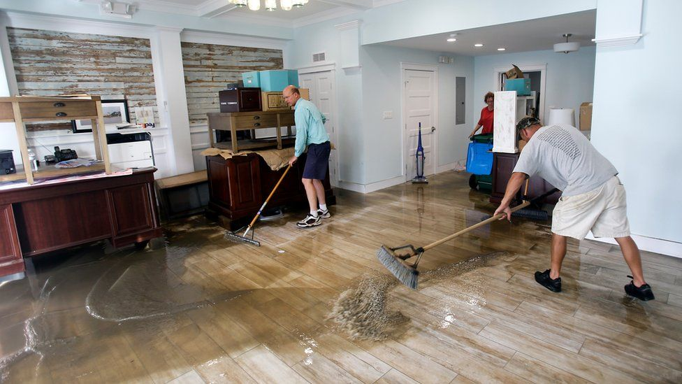 Shawn Stephenson, left, and Marshall Dimick clear water from a real estate office that was flooded by Hurricane Hermine Friday, 2 September 2016, in Cedar Key, Florida.
