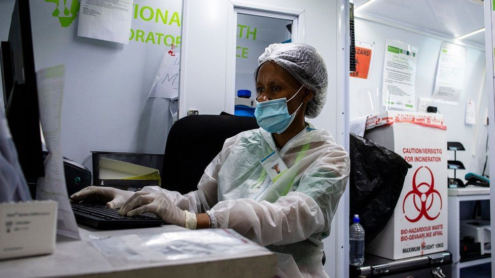 A medical staff member of the South Africa Health Department works at a computer in a mobile testing unit at O.R Tambo International Airport in Ekurhuleni on December 30, 3030, where passengers that have COVID-19 symptoms upon arrival are tested. (Photo by Luca Sola / AFP) (Photo by LUCA SOLA/AFP via Getty Images)