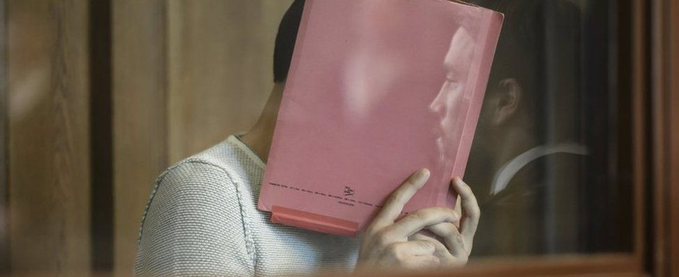 Svetoslav S holds a file in front of his face, during his trial in Berlin