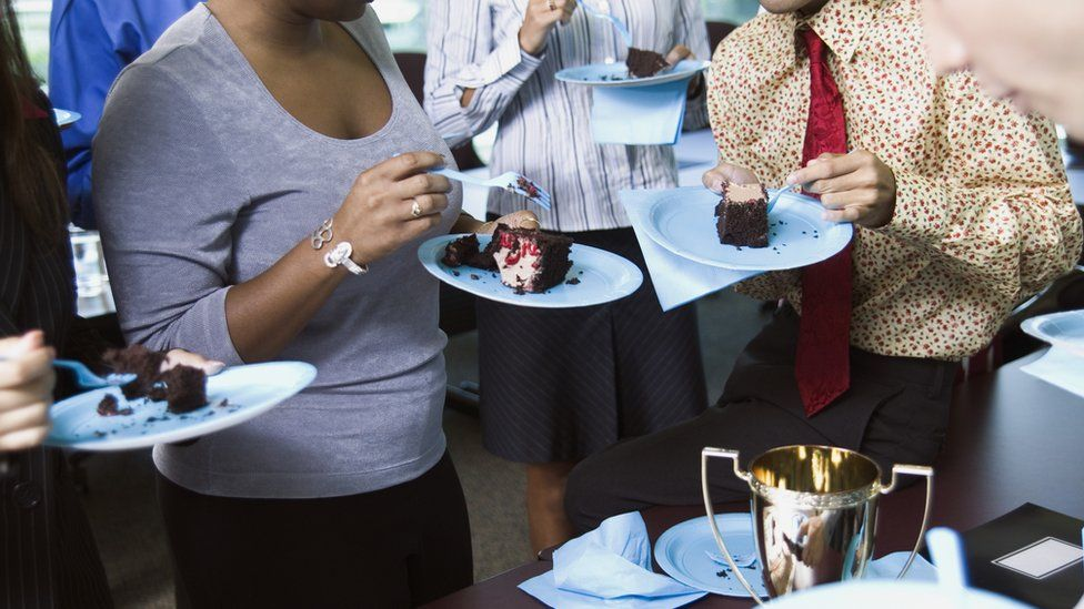 Office workers eating cake