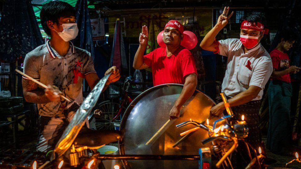 People bang their utensils and do the three-finger salute in a Yangon market on 5 February 2021