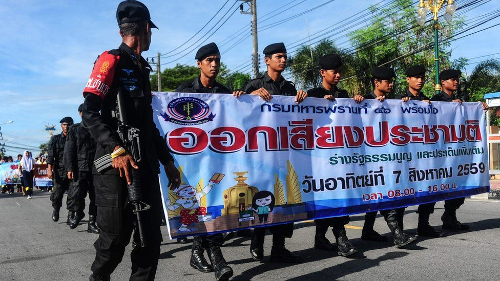 """Soldiers hold banners as they march during a campaign encouraging the public to vote in the upcoming referendum on Thailand""""s draft constitution in the southern restive province of Narathiwat on July 22, 2016"""