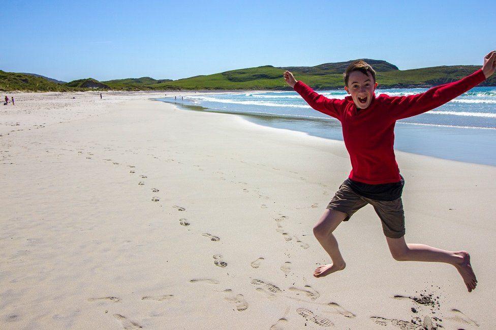 Boy jumping for joy on Vatersay beach