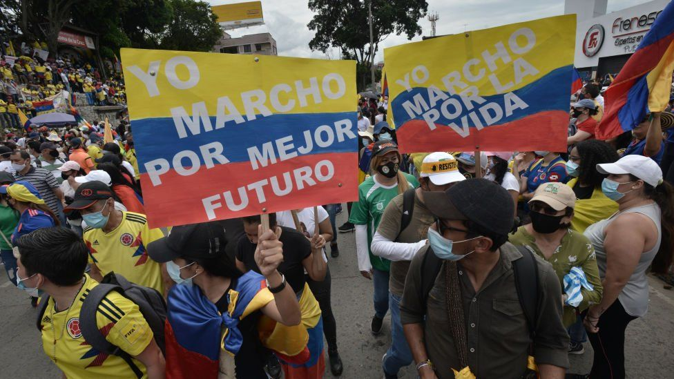 Demonstrators hold signs as they march through Cruz de la Loma towards Universidad del Valle during national strike against Ivan Duque's administration on May 12, 2021 in Cali, Colombia.