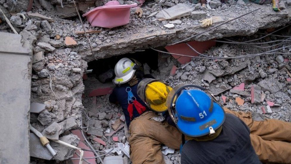 """Haitian firefighters search for survivors, under the rubble of a destroyed hotel, after Saturday""""s 7.2 magnitude quake, in Les Cayes, Haiti August 16, 2021"""