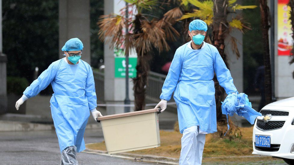 Medical staff carry a box as they walk at the Jinyintan hospital, where the patients with pneumonia caused by the new strain of coronavirus are being treated, in Wuhan