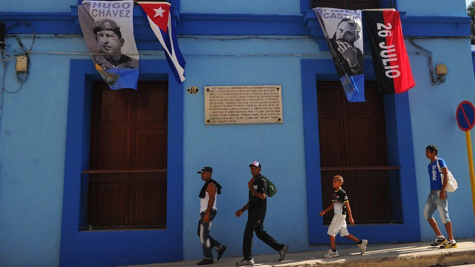 Flags with images of Cuban former president Fidel Castro (R) and late Venezuelan President Hugo Chavez are seen in Santiago de Cuba on July 25, 2015