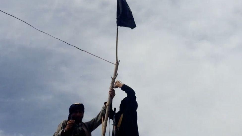 Screenshot of IS video showing two men hoisting a black flag