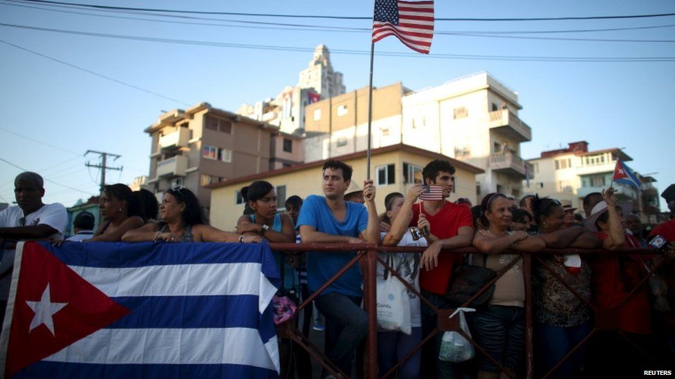 A man holds a US flag while gathering with others on a sidewalk near the US embassy (not pictured) in Havana, Cuba, on 14 August 2015.