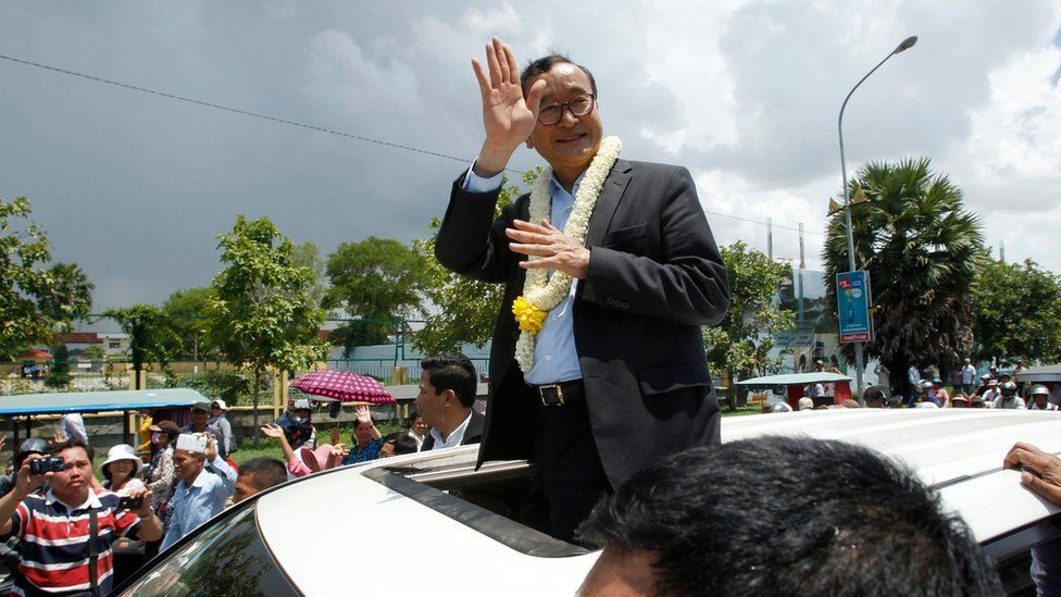 Sam Rainsy stands on the seat of a car, waving to crowds in Phnom Penh and wearing a flower garland around his neck