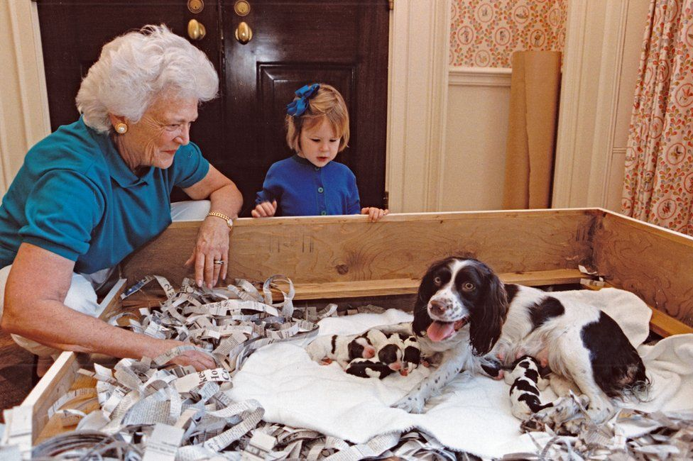 Barbara Bush and her granddaughter look at a dog who is feeding a littler of puppies