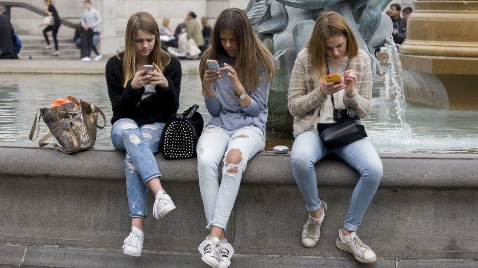 Teenage girls use smartphones