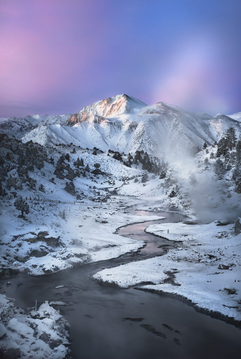 A river in front of a snow-covered mountain