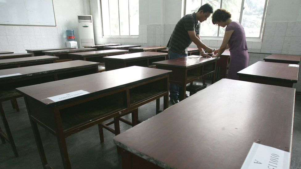 Teachers paste candidate numbers on desks in an exam room a day before the National College Entrance Examination June 6, 2007 in Xian of Shaanxi Province