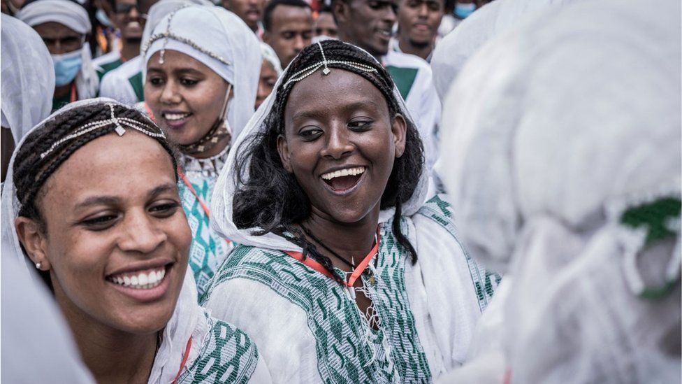 Smiling Ethiopian women dressed in traditional clothing celebrating the swearing in of Prime Minister Abiy Ahmed. They are part of a much larger crowd it seems. They are wearing intricate head accessories. They all look very happy.