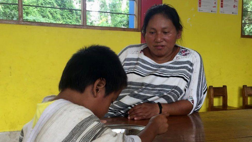 Romelia Rivera Italiano teaches a child at the local school