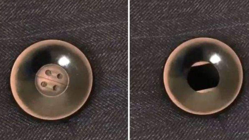 The camera behind the button of a man's jacket