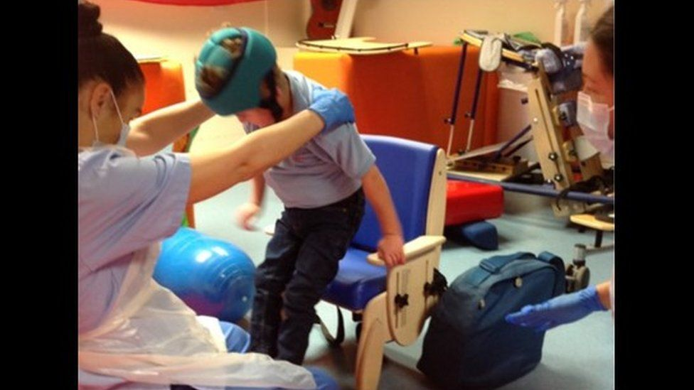 A pupil practising his sit-to-stand routine with his new chair with a teacher in PPE mask and gown assisting him.