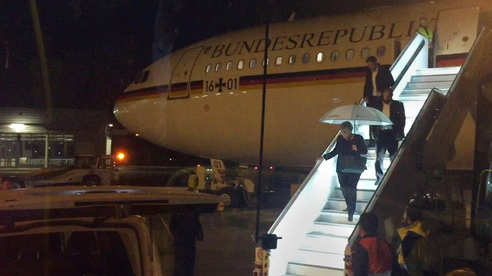 """German Chancellor Angela Merkel steps down from Airbus """"Konrad Adenauer"""" on late November 29, 2018 on the tarmac of Cologne""""s airport after an emergency landing"""