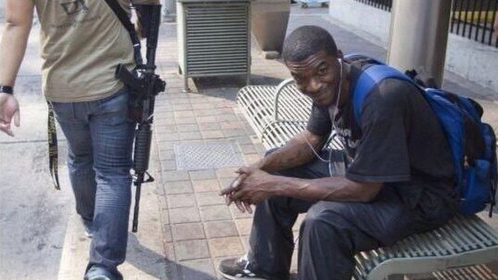 Tweet of black man sitting on bench as white man with assault rifle passes by