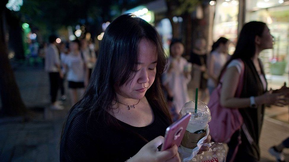 A Chinese woman uses her smartphone as she walks in a street in Beijing.