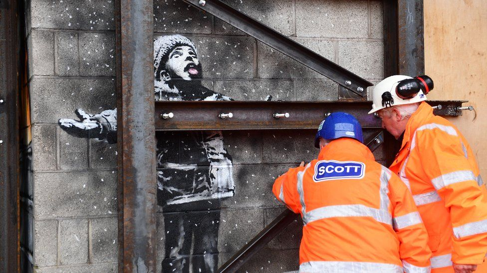 Contractors inspect the Banksy