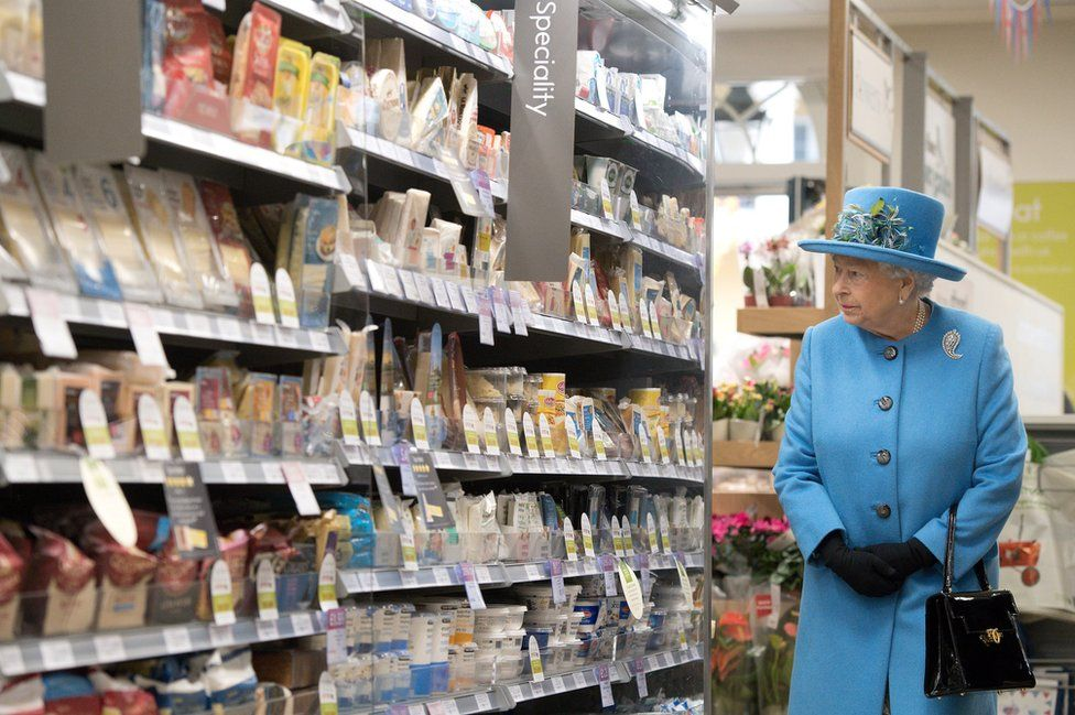 Queen Elizabeth II looks at products on the shelves at a Waitrose supermarket during a visit to the town of Poundbury on 27 October 2016