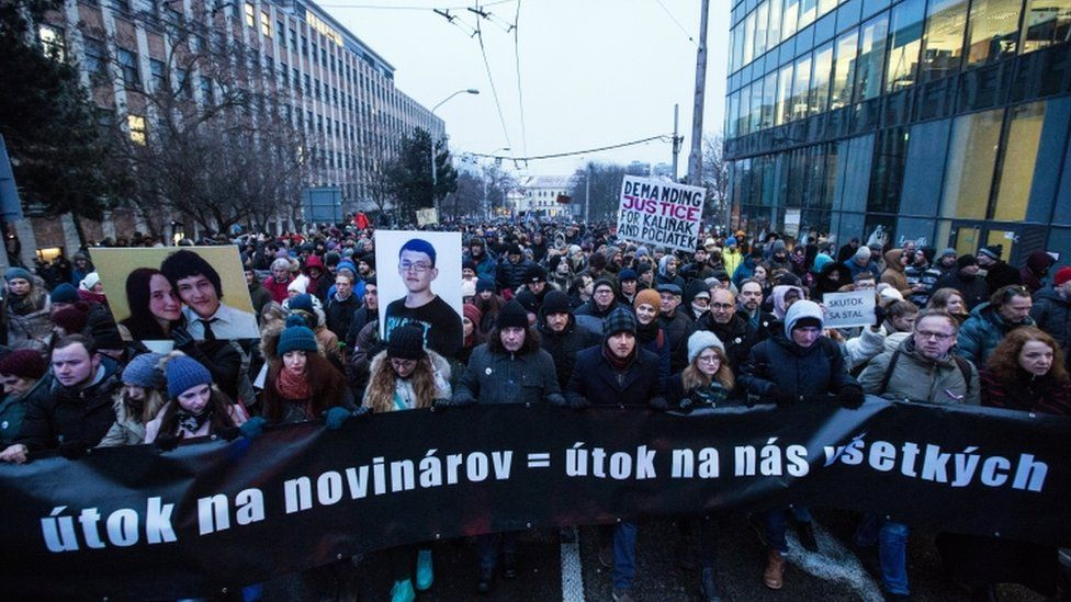 """Marchers with the banner saying """"an attack on journalists is an attack on us all"""""""