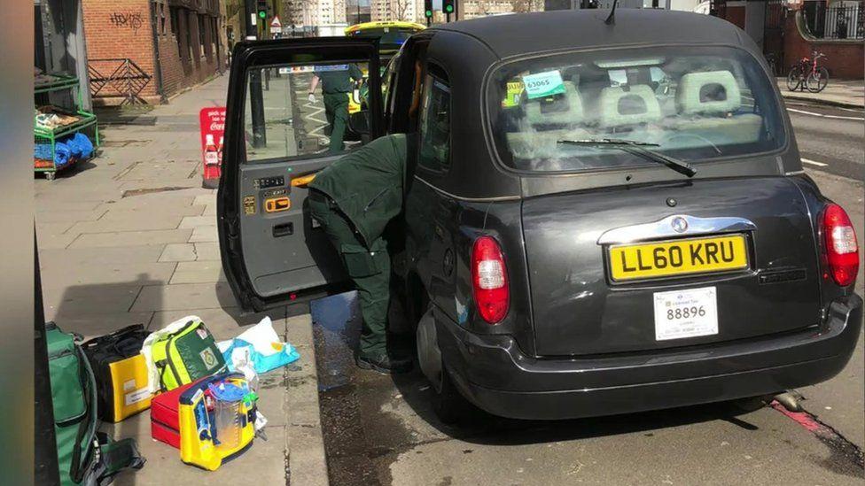 Paramedic beside taxi