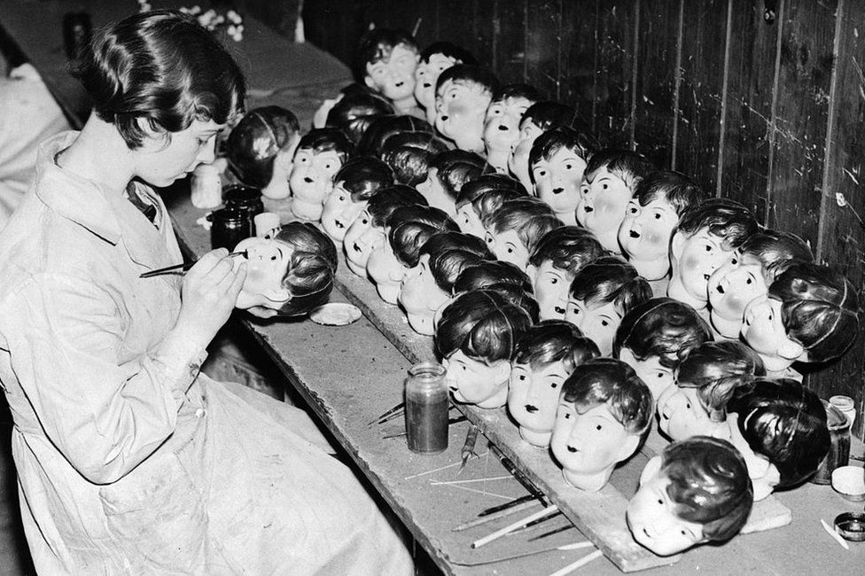 A worker painting celluloid dolls heads at a factory in Leicester in 1935