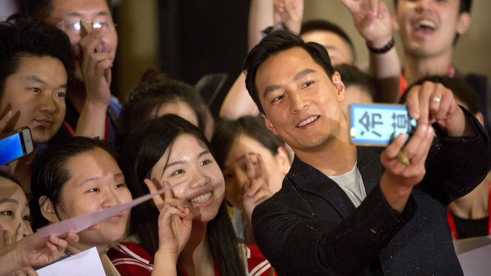 """Actor Daniel Wu poses for a selfie with Chinese fans at a red carpet event for the movie """"Warcraft"""" in Beijing, China, Wednesday, June 1, 2016."""