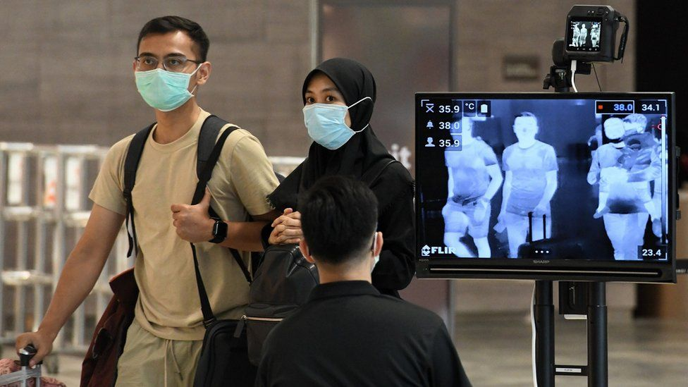 A couple, wearing protective facemasks amid fears about the spread of the COVID-19 novel coronavirus, walk past a temperature screening check at Changi International Airport in Singapore on February 27, 2020