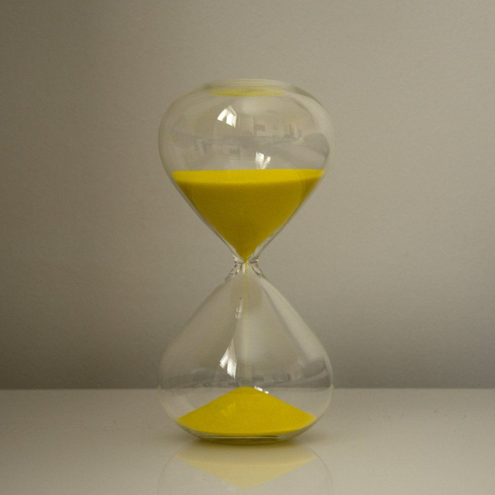 An image of a large hourglass with yellow sand inside