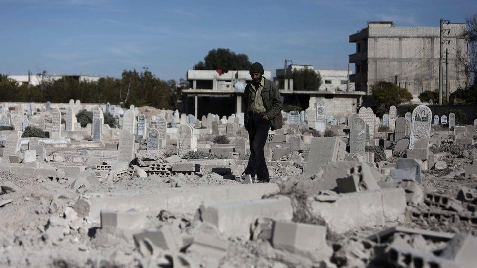 A man walks past a graveyard in Deir al-Asafir, outside Damascus, Syria (25 November 2015)