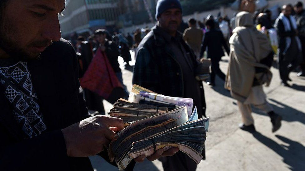 An Afghan money changer counts Afghani currency notes at the roadside in Kabul