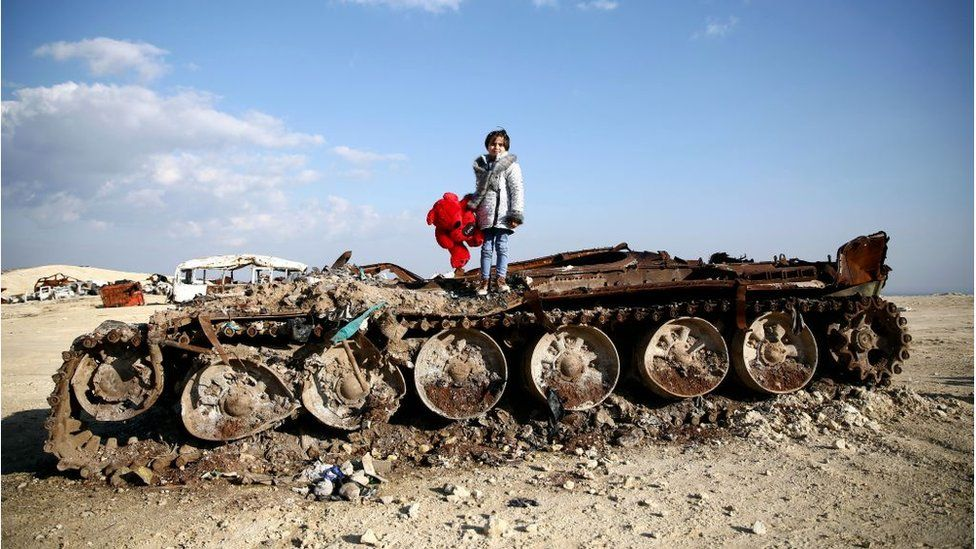Girl stands on remains of destroyed tank in Yazi Bagh, north-west Syria (Feb2019)