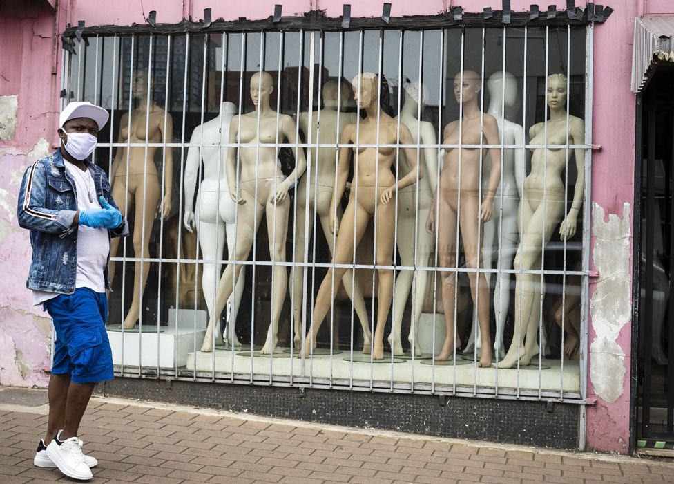 A masked man walking past a shop window with mannequins in Johannesburg, South Africa - Saturday 28 March 2020