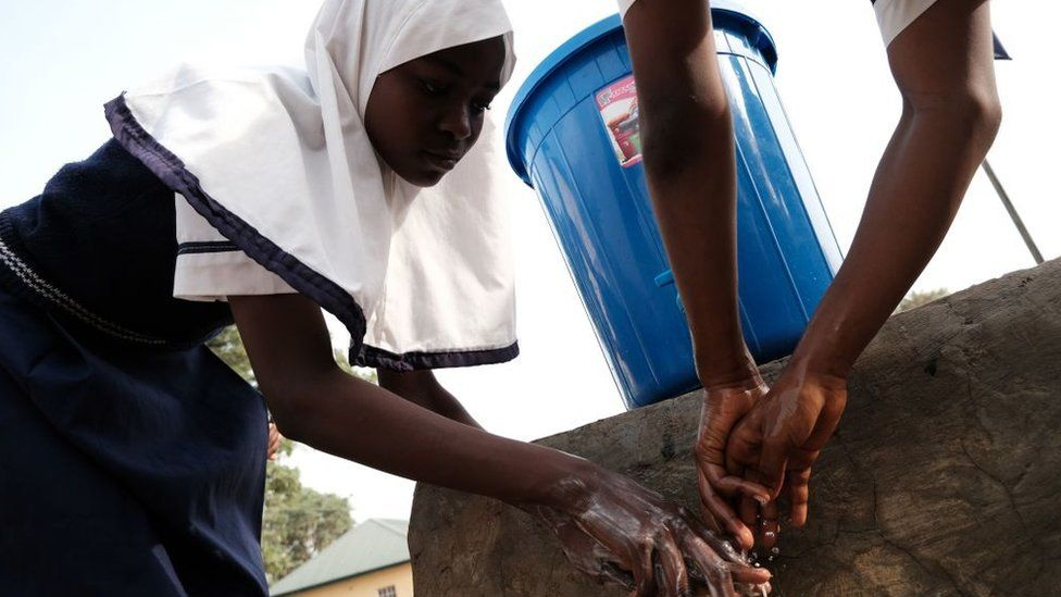A girl washes her hands in Abuja on 20 March