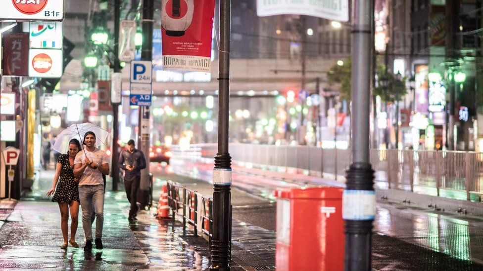 A couple protect themselves from the rain with an umbrella in the streets of Tokyo on 30 September 2018