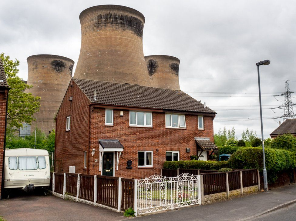 Houses situated in close proximity to the cooling towers at Ferrybridge Power Station. Knottingley, West Yorkshire.