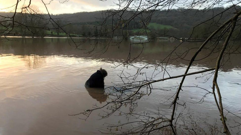 Woman trapped on roof of her car in flood water