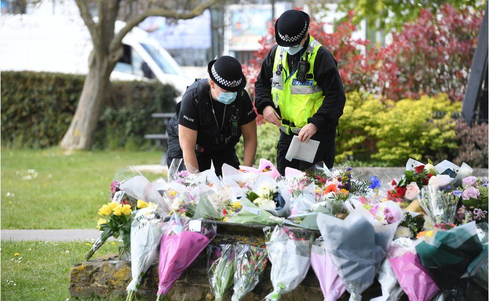 Police officers lay flowers at the scene