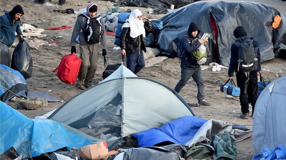 Migrants and volunteers clear part of the camp known as the Jungle