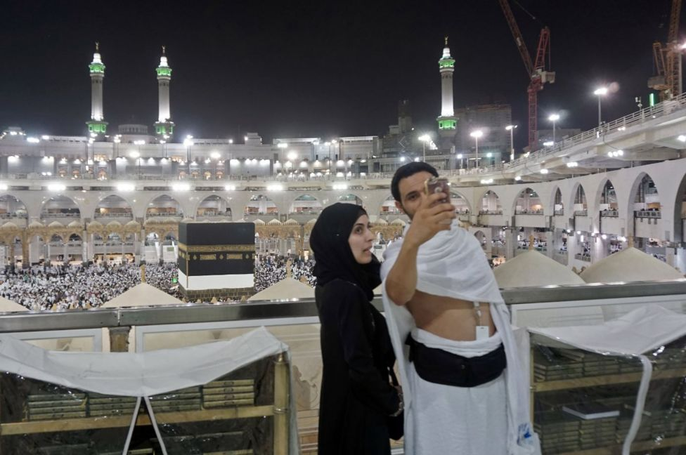 Muslim pilgrims take a selfie at the Grand Mosque in the holy Saudi city of Mecca, early on August 30, 2017, on the eve of the start of the annual Hajj pilgrimage. For the faithful it is a deeply spiritual journey, which for centuries every capable Muslim has been required to make at least once in their lifetimes. In the age of social media and live video streaming, it's now also an experience to be shared in real time. / AFP PHOTO / KARIM SAHIB (Photo credit should read
