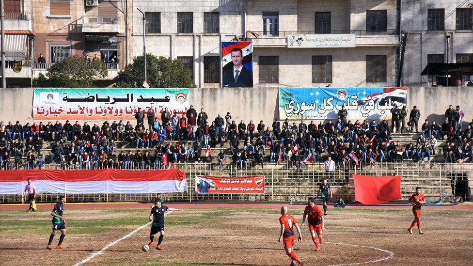 The stand by the sidelines is seen with a crowd - while a banner showing Syrian President Bashar Al-Assad hangs in the background