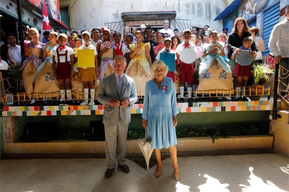 Prince Charles and Camilla pose in front of the children dressed in colourful costumes