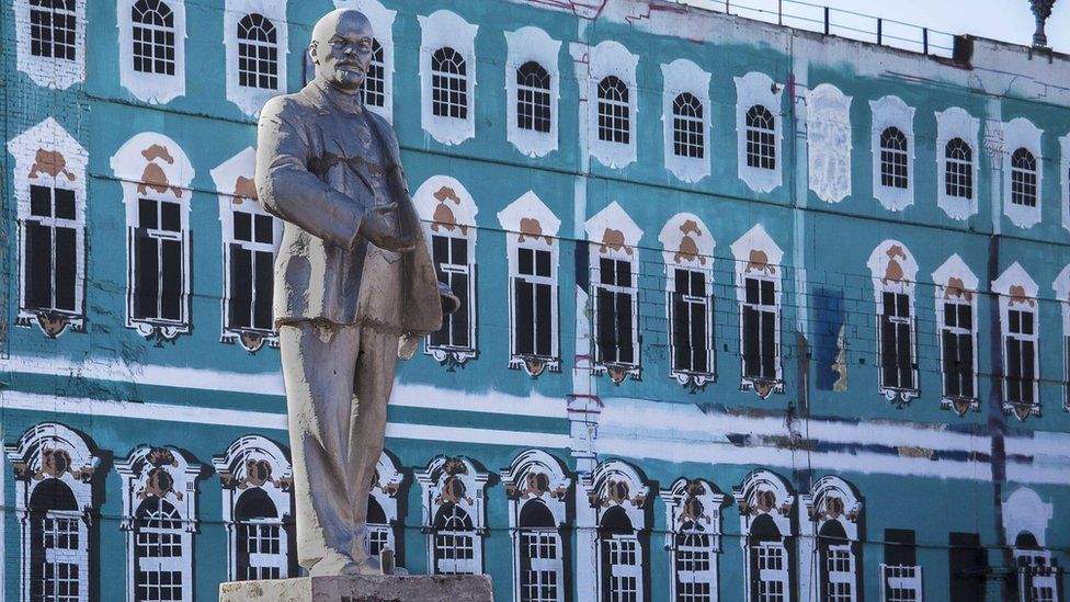 A statue of Lenin stands in front of a painted replica of the Winter Palace in St. Petersburg.