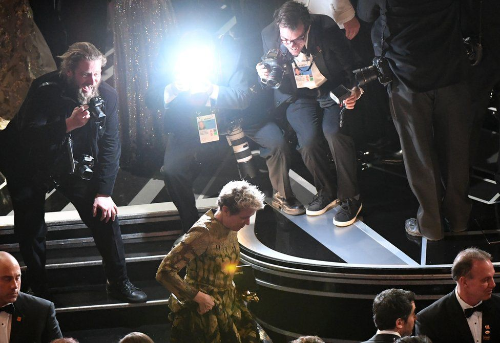 Frances McDormand leaves the stage with her Oscar whilst photographers take photos