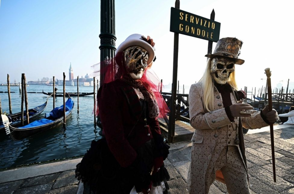 Masked revellers pose in Riva degli Schiavoni during the opening of the Venice Carnival