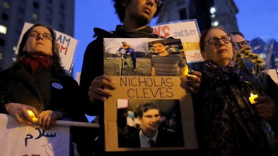 Bahij Chancey (C) stands with a sign featuring his friend, Nicholas Cleves, during a vigil in Foley Square in Manhattan, New York on 1 November 2017.